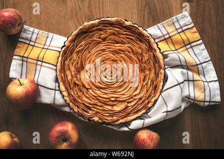 Apple pie decorated in shape of a rose flower, in a tray, on kitchen towel, surrounded by apples fruits, on vintage table. Above view of tatsy apple p - Stock Photo