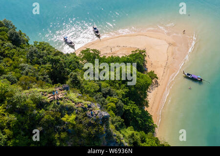 Aerial drone view of longtail boats passing between 2 small, rocky tropical islands - Stock Photo