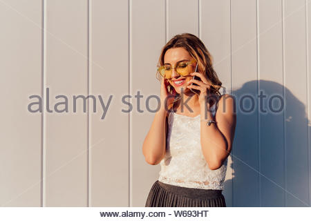 Happy attractive woman in yellow sunglasses having phone conversation, dressed in summer clothes, standing outdoors. - Stock Photo