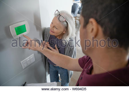 Service technician helping senior woman with digital thermostat - Stock Photo