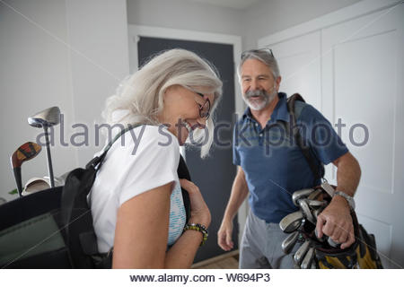 Happy senior couple with golf bags leaving home - Stock Photo