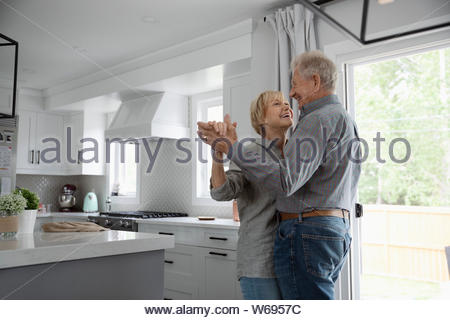 Happy, affectionate senior couple dancing in kitchen - Stock Photo