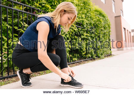 Young female runner tying shoelace on sidewalk - Stock Photo