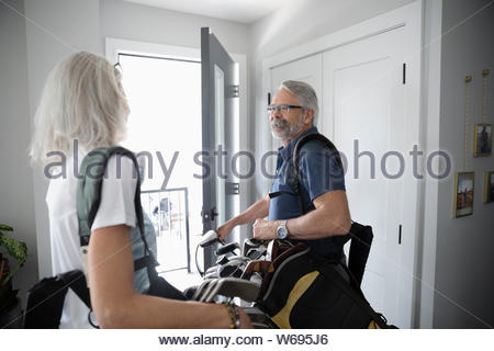 Senior couple with golf bags leaving home - Stock Photo