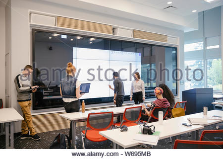 Student using smartboard in class with with teacher watching - Stock Photo