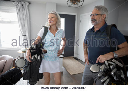 Senior couple with golf bags in living room - Stock Photo