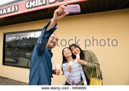 Family with camera phone taking selfie and eating ice cream outside drive-in - Stock Photo