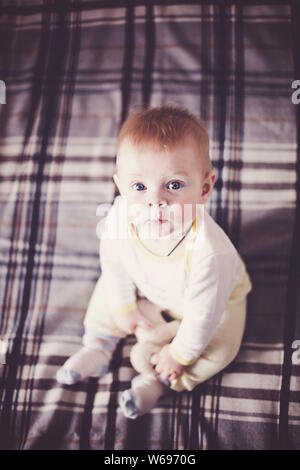 A cute blond baby with blue eyes in light clothes sits on a plaid bedspread on the bed and looks up. The child is holding a toy. - Stock Photo