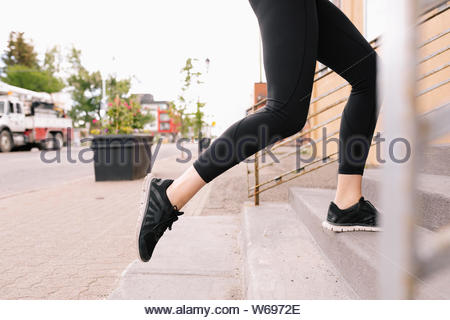 Young woman running up urban steps - Stock Photo