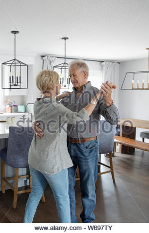 Affectionate senior couple dancing in kitchen - Stock Photo