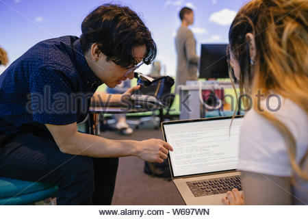 Student helping friend with computer code on laptop in VR class - Stock Photo