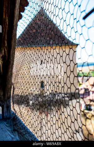 Abstract picture of part of the bergfried or donjon of the Calnic Citadel, Alba County, Transylvania, Romania behind wire mesh - Stock Photo