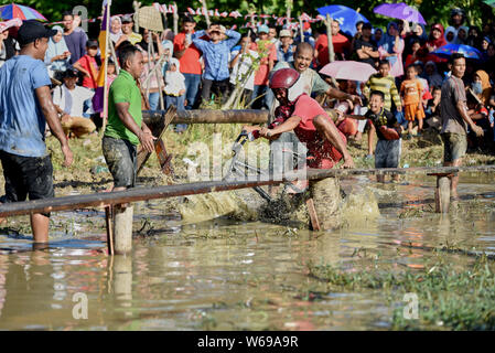Banda Aceh, Indonesia - August 17, 2017: Commemorate Indonesia's independence day. Participants were passing a wooden bridge over a pond with bicycle - Stock Photo