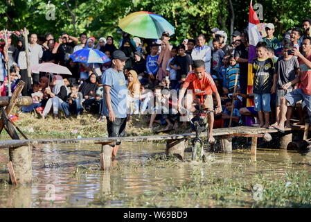 Banda Aceh, Indonesia - 07/17, 2017 : Teenagers are compete of passing a wooden bridge over a pond with bicycle to commemorate Independence day - Stock Photo
