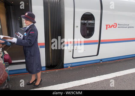 Saint Petersburg, Russia - June 06, 2017: an uniformed attendant orients passengers boarding the high speed train from Saint Petersburg to Moscow - Stock Photo