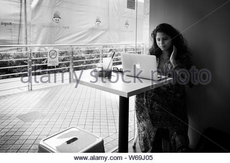 Singapore - October 21st 2015: Black & white image of a young Indian woman sat in a coffee shop with an iced coffee doing work on an apple macbook lap - Stock Photo