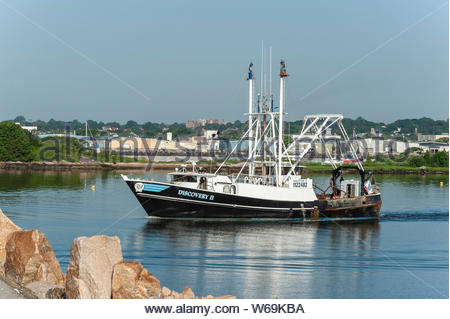 New Bedford, MA, USA - July 26, 2019: Scalloper Discovery II, hailing port New York, NY, in New Bedford inner harbor approaching hurricane barrier - Stock Photo