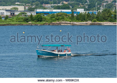 New Bedford, MA, USA - July 26, 2019: Tour boat cruising past Palmer Island in New Bedford harbor as Captain Kathy points out some harbor highlights - Stock Photo