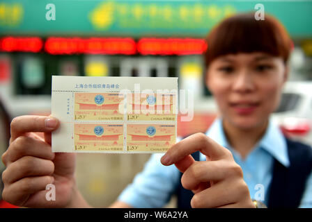 A Chinese employee shows a sheet of stamps commemorating the 18th Shanghai Cooperation Organization (SCO) summit at a China Post Office in Xinle city, - Stock Photo