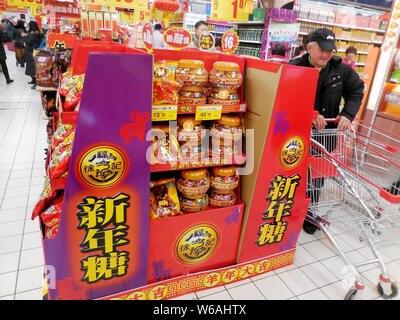--FILE--A customer walks past a counter of Hsu Fu Chi at a supermarket in Beijing, China, 24 January 2015.   The list of fast foods that can be bought - Stock Photo