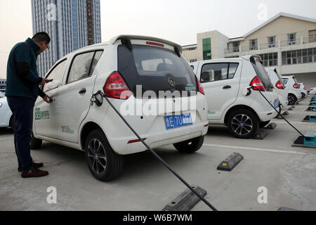 --FILE--A local resident uses an electric vehicle (EV) of Chinese car-sharing service Mate Go in Dongying city, east China's Shandong province, 22 Mar - Stock Photo