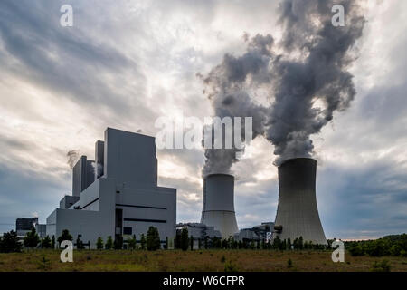 The buildings and steaming cooling towers of a coal-fired power plant in agricultural landscape
