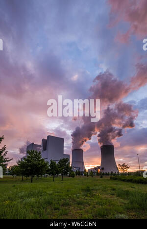 The buildings and steaming cooling towers of a coal-fired power plant in agricultural landscape at sunset
