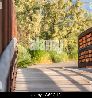 Square Close up of a bridge with metal guardrail and wood deck on a sunny day - Stock Photo