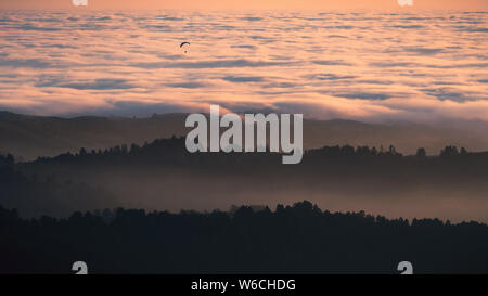 Sunset view of layered hills and valleys covered by a sea of clouds in Santa Cruz mountains; paraglider visible above the clouds; San Francisco bay ar - Stock Photo