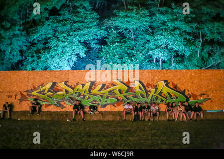 Brezje, Croatia - 19th July, 2019 : Wooden wall with graffiti and audience resting next to it during the Forestland, ultimate forest electronic music - Stock Photo