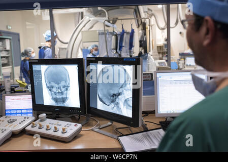 Clermont-Ferrand (central France). Radiology department at university hospital. Radiologist conducting an angiography in the interventional imaging ro - Stock Photo