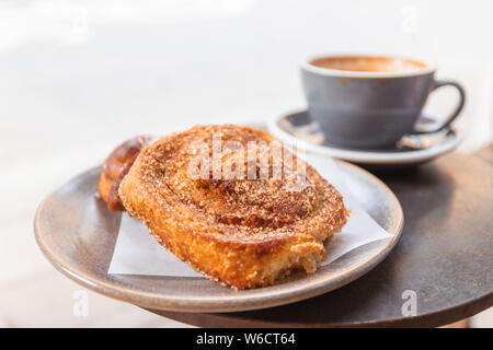 Warm cinnamon bun with icing sugar with a cup of coffee lying on the table in a street cafe. - Stock Photo