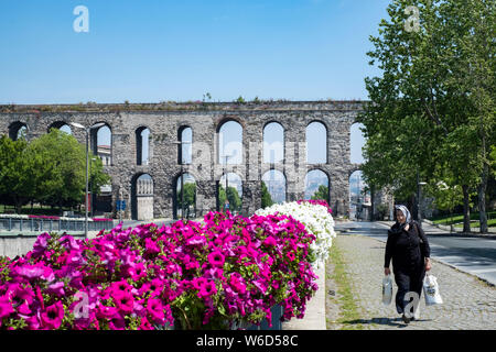 The Valens Aqueduct built by the Romans and towering over the modern city of Istanbul, Turkey in the springtime on a sunny day. - Stock Photo