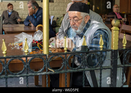 An elderly man in a hat and vest crafts worry beads and necklaces on a cafe table in central Istanbul, Turkey - Stock Photo