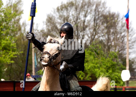 A knight rides down the tournament field to catch a ring with his lance at the Medieval Centre in Nykøbing Falster, Denmark. The Medieval Centre is built around the village Sundkøbing at a fjord as it was around the year 1400. Houses are authentically designed and built with the people who populate the village, men, women, children, peasants, craftsmen, warriors and knights etc dressing and work as they would back in 1400.  Canons and large trebuchets can be seen firing missiles with knights in armour on horseback competing with lances and swords, dyers colour textiles with plants and in the c - Stock Photo