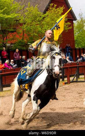 A galloping knight celebrating his victory at the tournament track at the outdoor Medieval Centre in Nykøbing Falster, Denmark. The Medieval Centre is built around the village Sundkøbing at a fjord as it was around the year 1400. Houses are authentically designed and built with the people who populate the village, men, women, children, peasants, craftsmen, warriors and knights etc dressing and work as they would back in 1400.  Canons and large trebuchets can be seen firing missiles with knights in armour on horseback competing with lances and swords, dyers colour textiles with plants and in th - Stock Photo