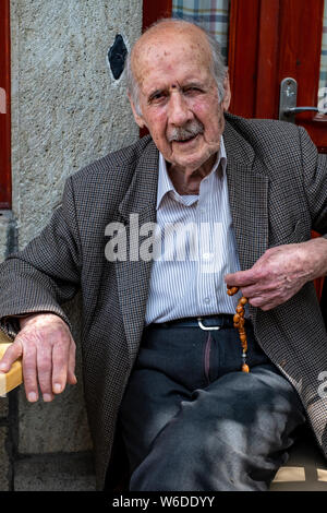 An elderly Greek man sit in the shade of a village cafe observing the passing scene while playing with his worry beads - Stock Photo