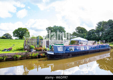 Moored narrow boat called Shawthing Jesabel with private garden,and mess, on the Trent and Mersey canal in Cheshire UK - Stock Photo