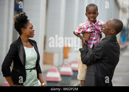 Happy young father holding his son in arms, mother, father and child having fun together outdoors. dad and child laugh and hug each other - Stock Photo