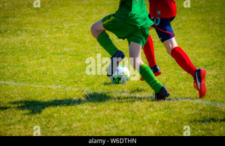 Two opposing players chasing a football. The athletes in the image are 14 year old boy soccer players. This shot catches them both in action. - Stock Photo