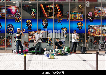 Street musicians playing in front of a videogame shop at Akihabara district - Stock Photo