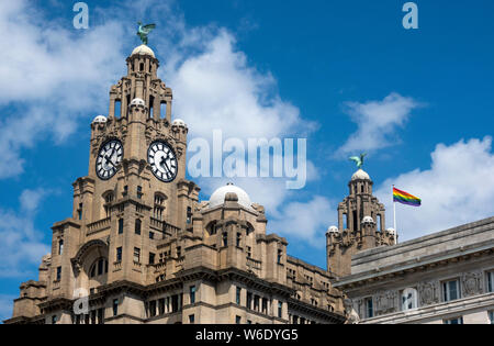 The LBGT flag flying over the Liver Building at Pier Head next to the Mersey in Liverpool, UK - Stock Photo