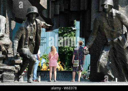 Warsaw Poland - Thursday 1st August - A Polish family visits the Warsaw Uprising monument in Warsaw as Poland commemorates the 75th Anniversary of the Warsaw Uprising ( Powstanie Warszawskie ) against the occupying German Army on 1st August 1944 - the Warsaw Uprising resistance fighters of the Home Army ( Armia Krajowa  - AK ) struggled on for 63 days against the Nazi forces before capitulation as the advancing Soviet Army waited across the nearby River Vistula. Photo Steven May / Alamy Live News - Stock Photo