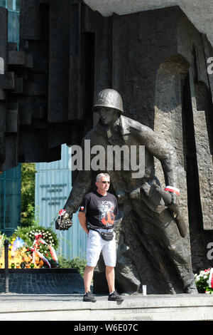 Warsaw Poland - Thursday 1st August - A Polish man stands proudly in front of the Warsaw Uprising monument in Warsaw as Poland commemorates the 75th Anniversary of the Warsaw Uprising ( Powstanie Warszawskie ) against the occupying German Army on 1st August 1944 - the Warsaw Uprising resistance fighters of the Home Army ( Armia Krajowa  - AK ) struggled on for 63 days against the Nazi forces before capitulation as the advancing Soviet Army waited across the nearby River Vistula. Photo Steven May / Alamy Live News - Stock Photo