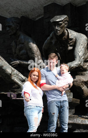 Warsaw Poland - Thursday 1st August - A young family proudly wearing a patriotic armband pose in front of the Warsaw Uprising monument in Warsaw as Poland commemorates the 75th Anniversary of the Warsaw Uprising ( Powstanie Warszawskie ) against the occupying German Army on 1st August 1944 - the Warsaw Uprising resistance fighters of the Home Army ( Armia Krajowa  - AK ) struggled on for 63 days against the Nazi forces before capitulation as the advancing Soviet Army waited across the nearby River Vistula. Photo Steven May / Alamy Live News - Stock Photo