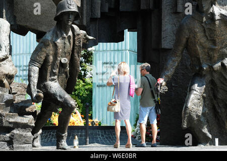 Warsaw Poland - Thursday 1st August - Visitors infront of the Warsaw Uprising monument in Warsaw as Poland commemorates the 75th Anniversary of the Warsaw Uprising ( Powstanie Warszawskie ) against the occupying German Army on 1st August 1944 - the Warsaw Uprising resistance fighters of the Home Army ( Armia Krajowa  - AK ) struggled on for 63 days against the Nazi forces before capitulation as the advancing Soviet Army waited across the nearby River Vistula. Photo Steven May / Alamy Live News - Stock Photo