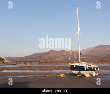 Barmouth, Gwynedd. Low tide in the Mawddach Estuary has left a yacht beached in the harbour. A railway bridge and mountains are in the background. - Stock Photo