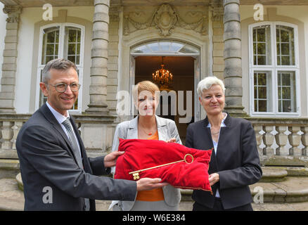 Brandenburg, Germany. 01 August 2019, Brandenburg, Wiepersdorf: Steffen Skudelny, Chairman of the German Foundation for Monument Conservation (DSD), symbolically hands over the key to Wiepersdorf Castle to Martina Münch (M, SPD), Minister of Culture of the State of Brandenburg and Annette Rupp, founding commissioner of the Cultural Foundation. Since today the castle is under the sponsorship of the state of Brandenburg. Credit: dpa picture alliance/Alamy Live News - Stock Photo