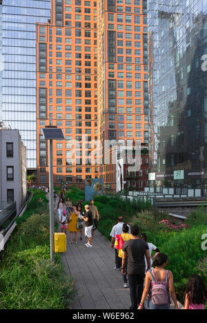 Manhattan High Line, view of people on a summer evening walking the High Line park in the Chelsea neighborhood of Manhattan, New York City.