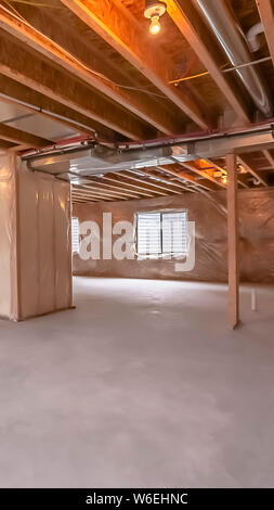 Vertical frame Home under construction with interior framing beams and plastic covered wall - Stock Photo